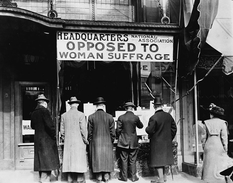 """Photograph shows men looking at material posted in the window of the National Anti-Suffrage Association headquarters; sign in window reads """"Headquarters National Association Opposed to Woman Suffrage""""."""