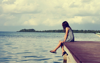 girl sits on a dock looking out on a lake