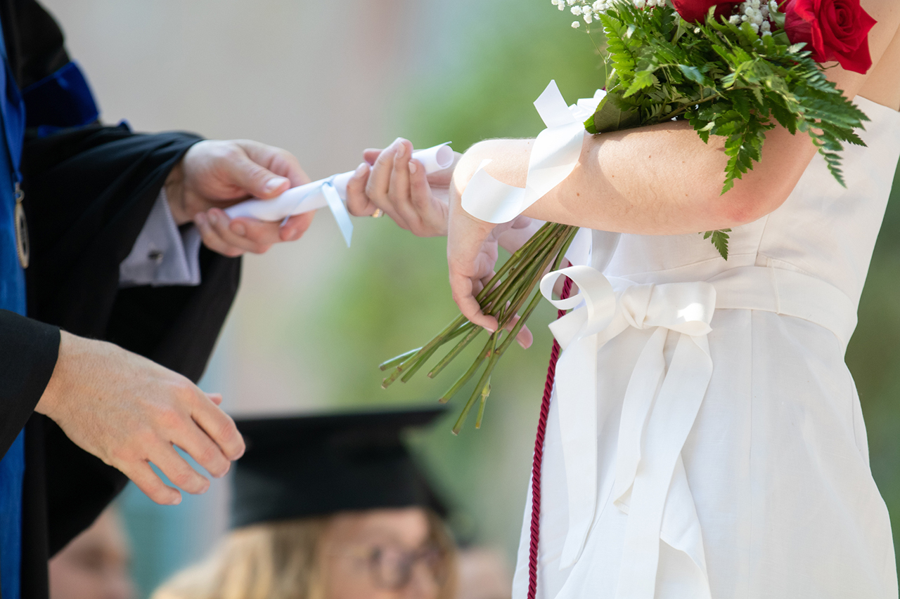 a faculty member hands a female graduate a diploma