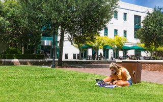 a student sits on the grass outside addlestone library looking at a laptop