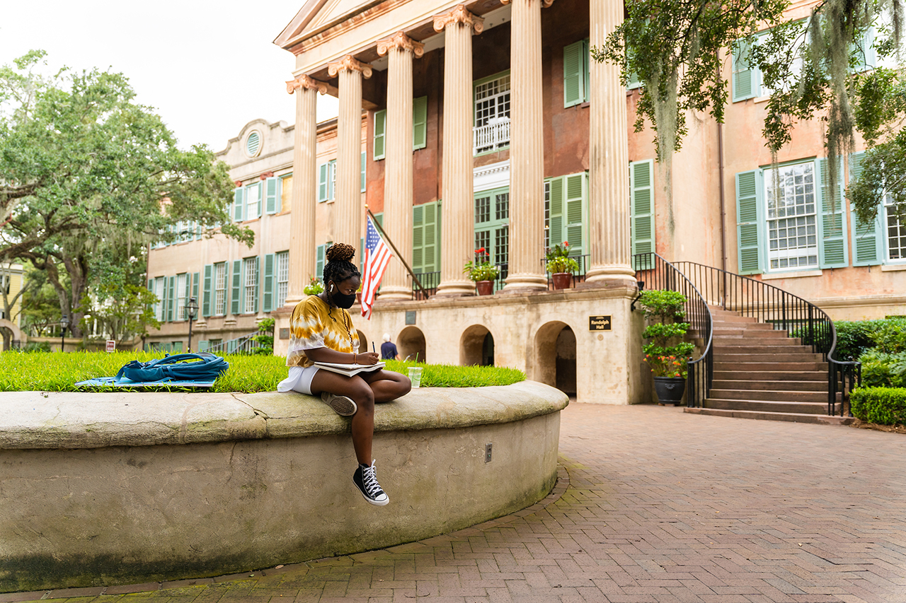 a girl sits on the cistern at the college of charleston campus