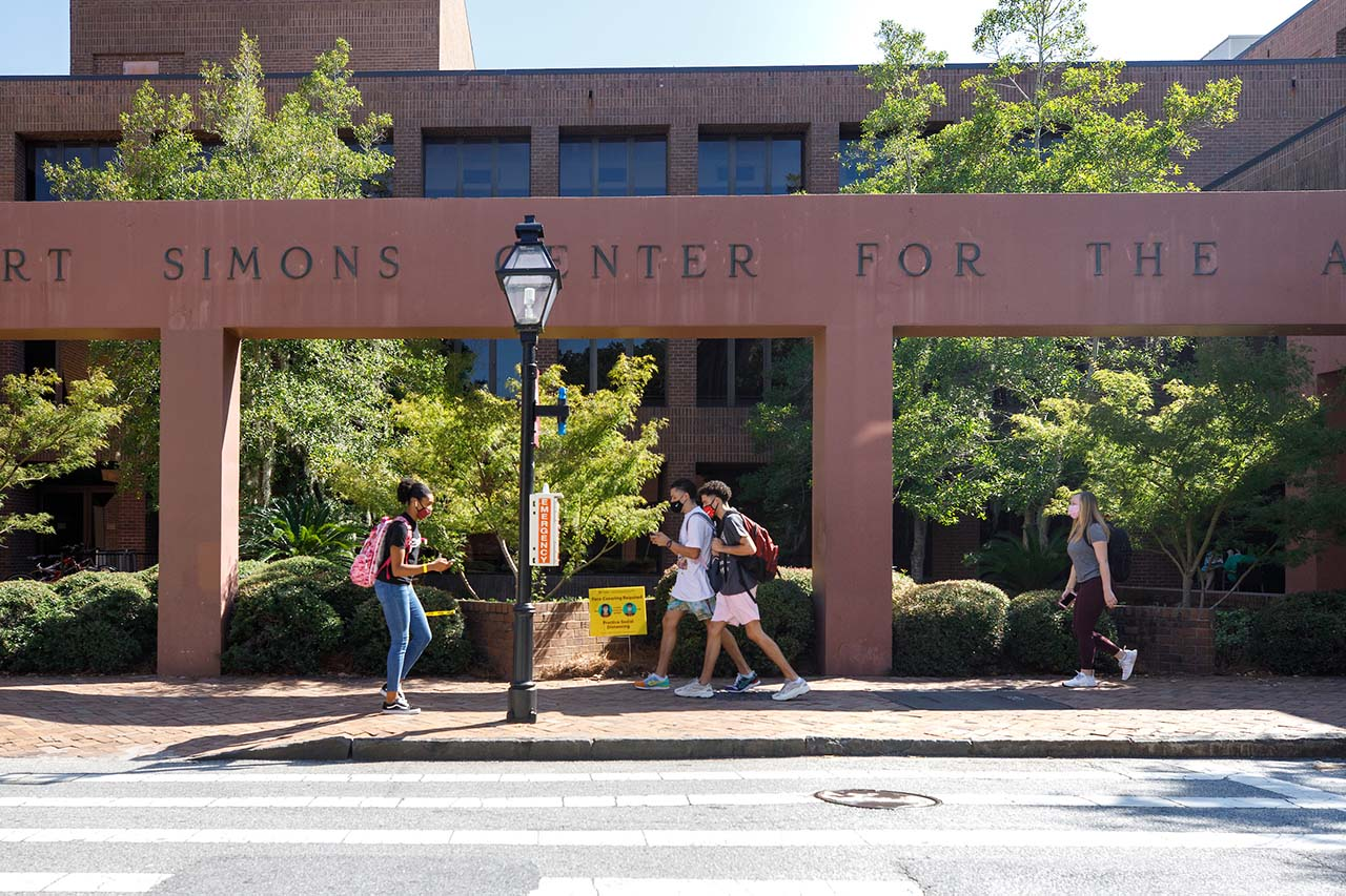 students walk along st. philip street on the college of charleston campus