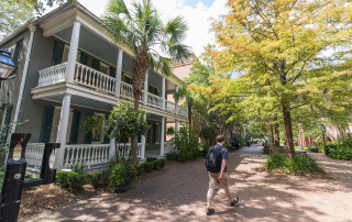 a student walks on the brick walkway of cougar mall at the college of charleston campus