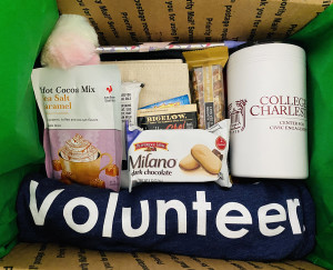 box with hot cocoa mix, cookies, a t-shirt and a water bottle