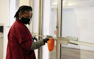Barbara Simmons cleans a door in college lodge residence hall