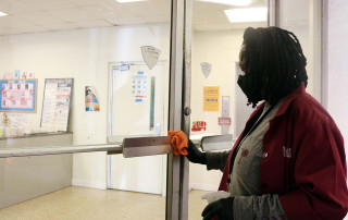 barbara simmons cleans a door at college lodge