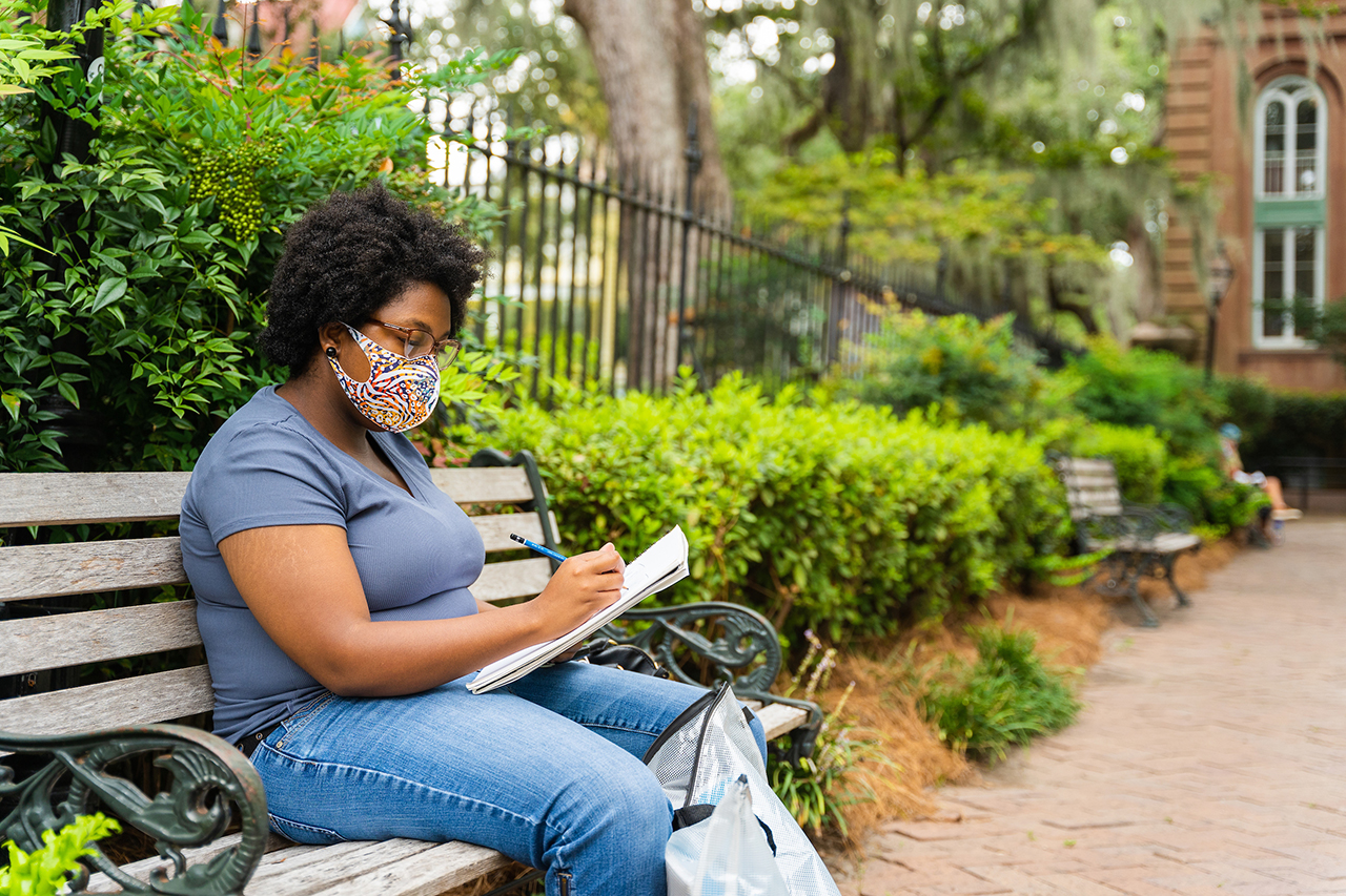 a student takes notes on a park bench outside