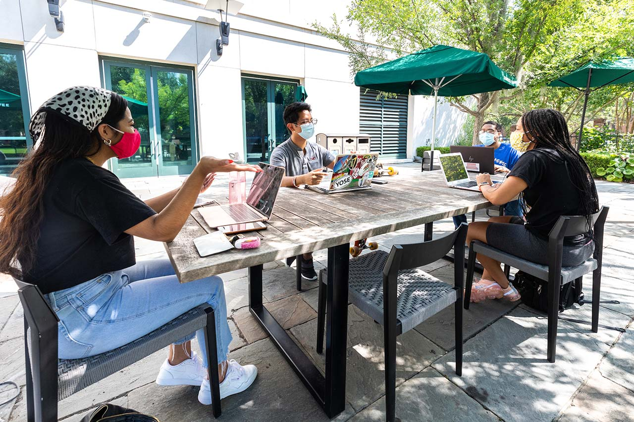 students wearing masks talk on the patio of addlestone library