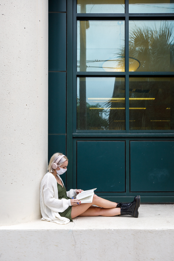 A CofC Student wears a mask while studying in an outdoor alcove at the Addlestone Library.