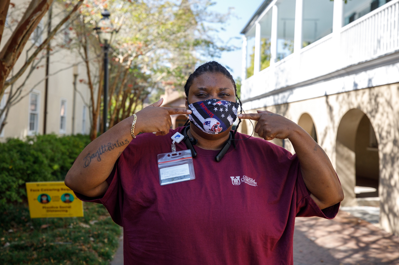 A campus employee wears a Patriots mask.