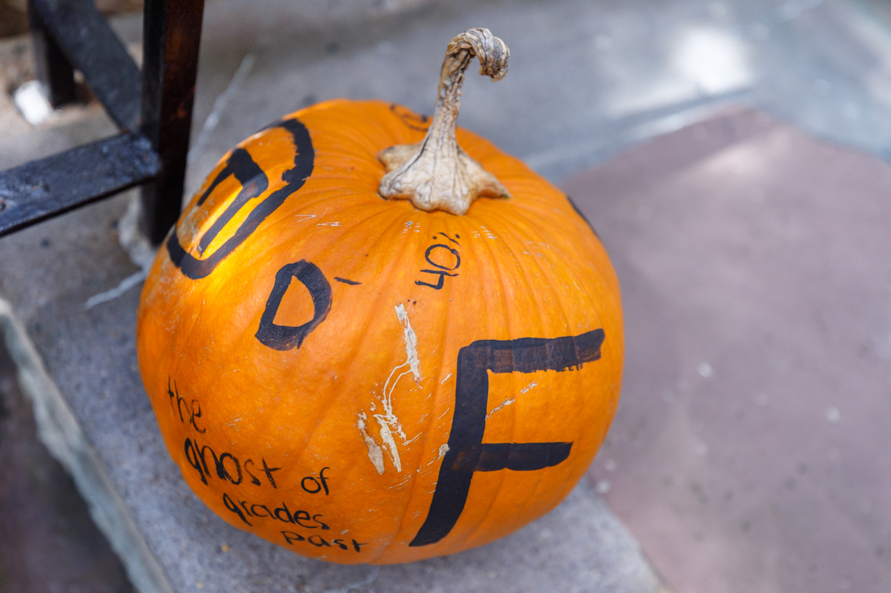"""The ghosts if Grades Past"" halloween pumpkin sits on the steps of the Honors College."