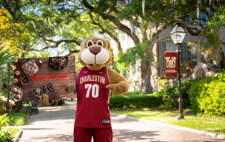 clyde the cougar holding a cougar cookbook