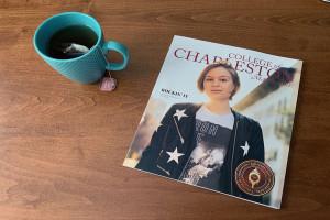 cofc magazine cover on a desk next to a coffee mug