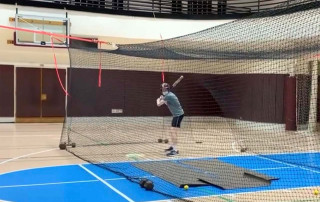student in a batting cage in silcox gym