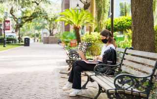 student studies on a bench on cofc campus