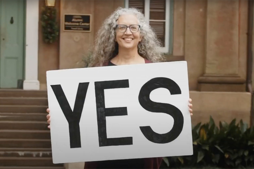 woman holds a sign that says yes