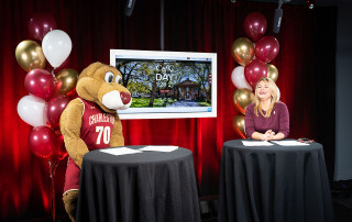 cofc alumna Lauren Arnott '13 and clyde the cougar during cofc day
