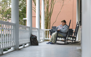 student john broome studies on the porch of the honors college