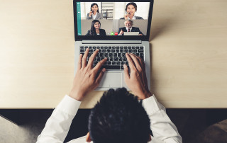 a man sits at a laptop looking at a screen where other people are in view for a virtual meeting