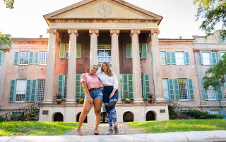 two female students pose in front of randolph hall at the college of charleston