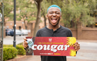 a student holds a cougar sign
