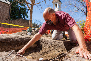 Geology and archaeology professor Scott Harris examines the layers of a dig site on the College of Charleston campus.