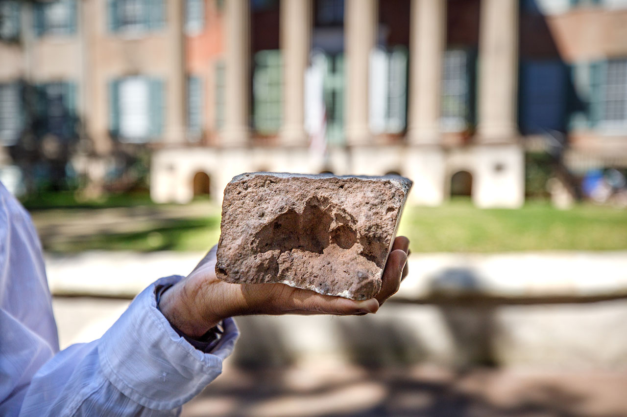 a hand holds a brick with fingerprints in front of randolph hall at the college of charleston