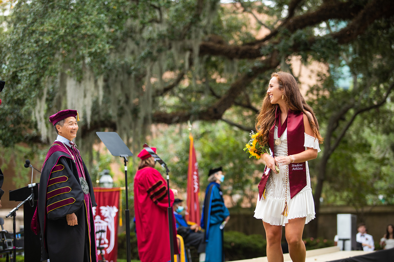 a student celebrates commencement at the college of charleston