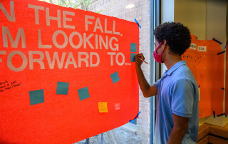 a student signs a message board in berry hall