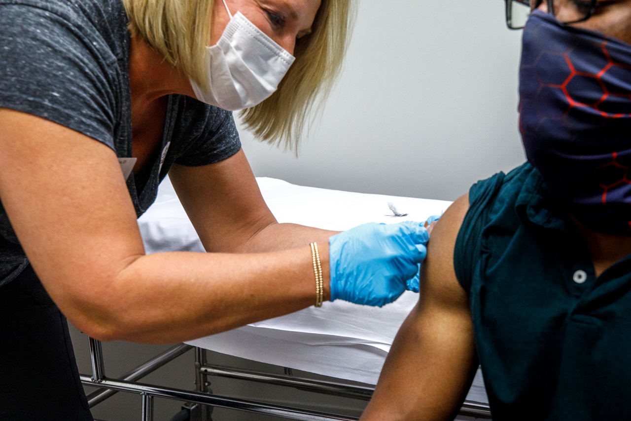 The nurse puts a band-aid on after the CofC student gets the first of two shots of the Moderna COVID-19 Vaccine.