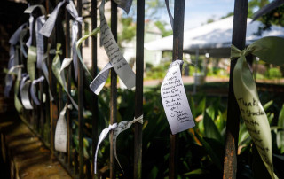 ribbons with messages tied to fence