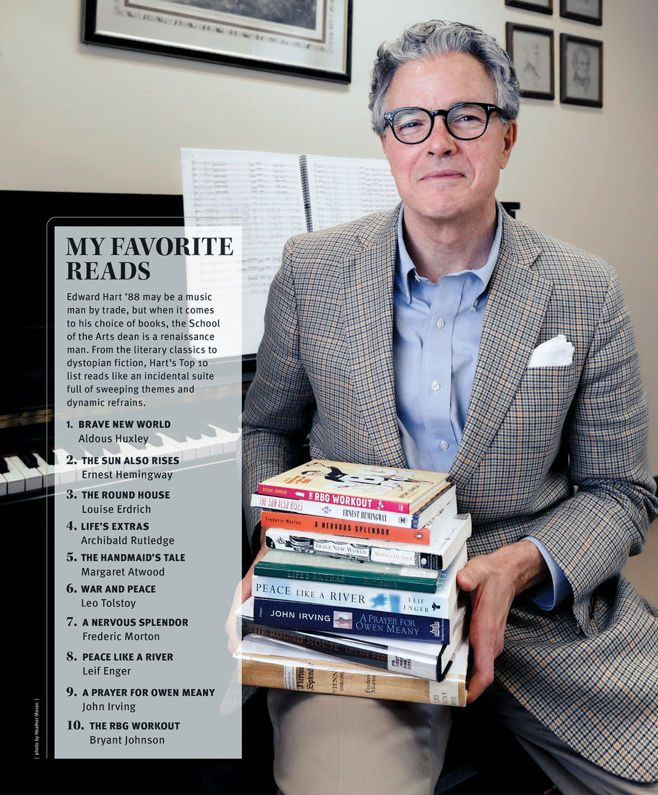 school of the arts dean Edward Hart holds his favorite books including the RBG workout, brave new world, the sun also rises, the handmaid's tale, war and peace and a prayer for owen meany