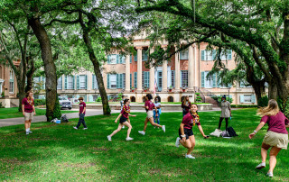 students run and play a game in the cistern yard at the college of charleston