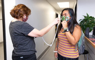 a student gets her temperature checked