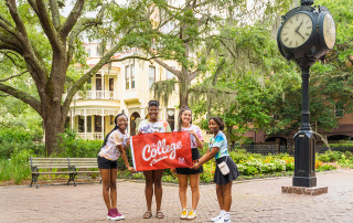 students hold a college of charleston sign