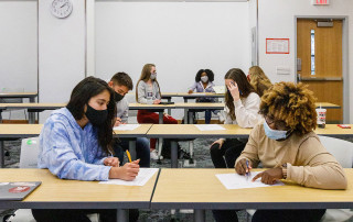 students in a classroom wearing face coverings