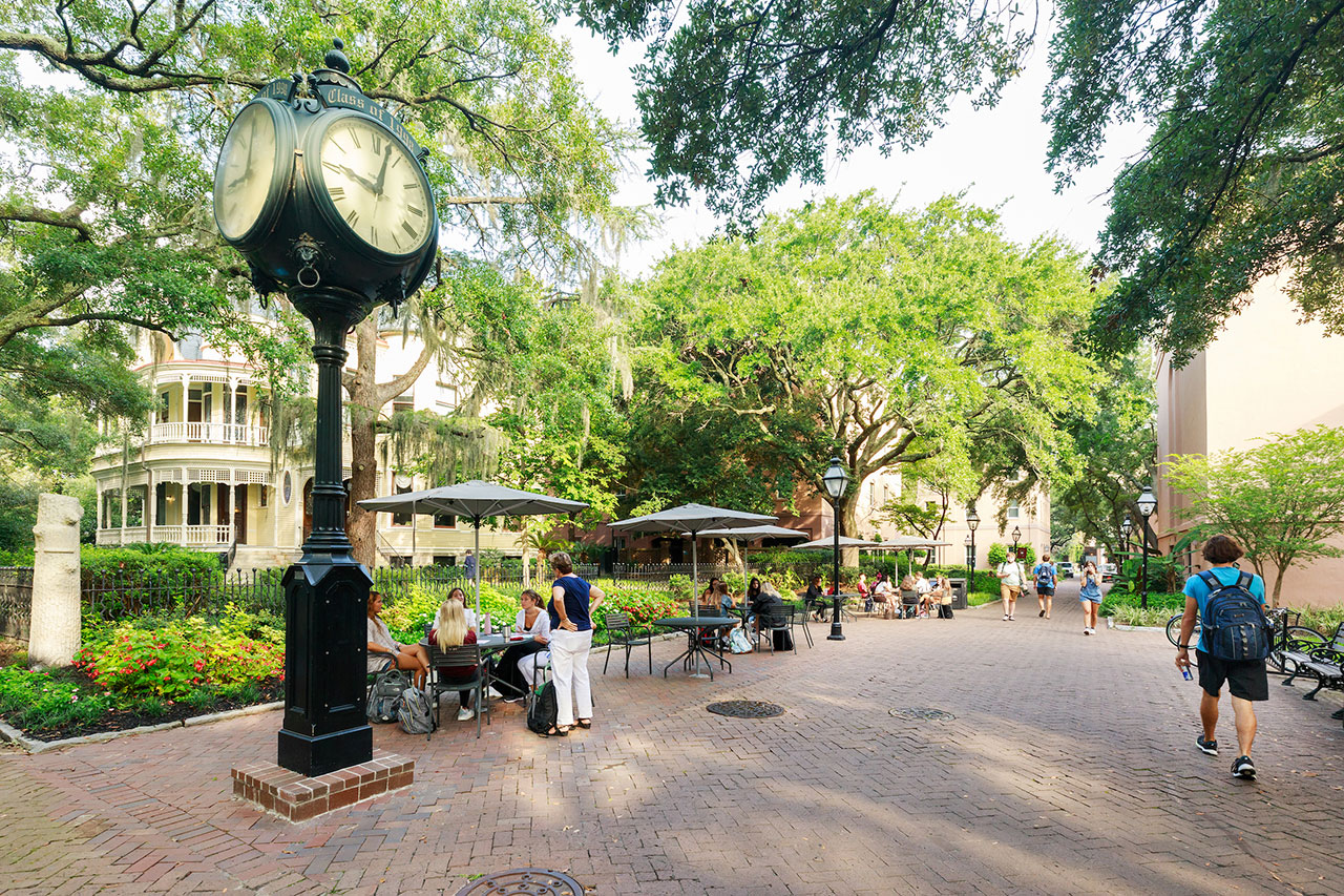 students sit near a large clock on the college of charleston campus